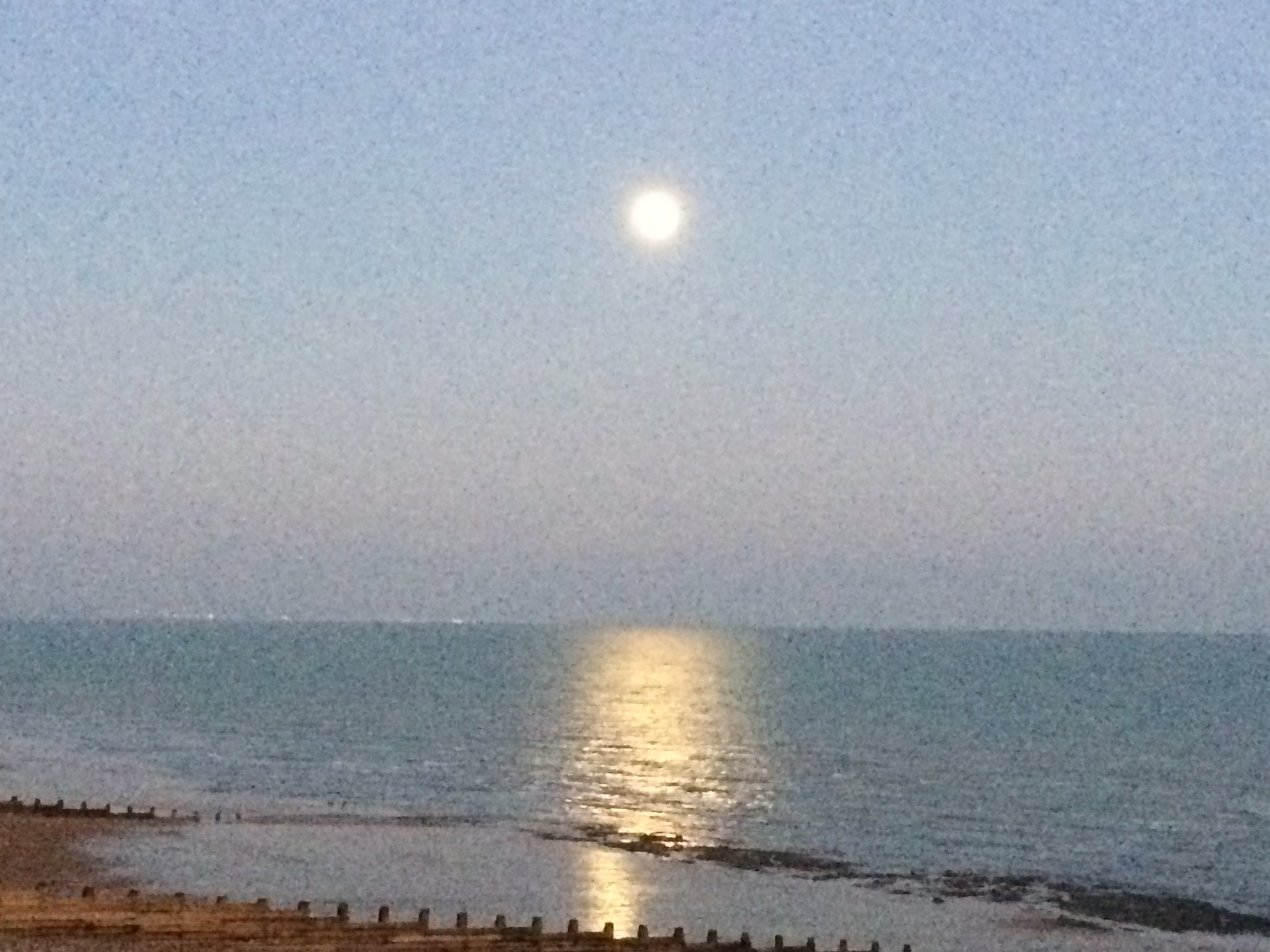 Full moon rising in the southeastern sky over the sea at Eastbourne