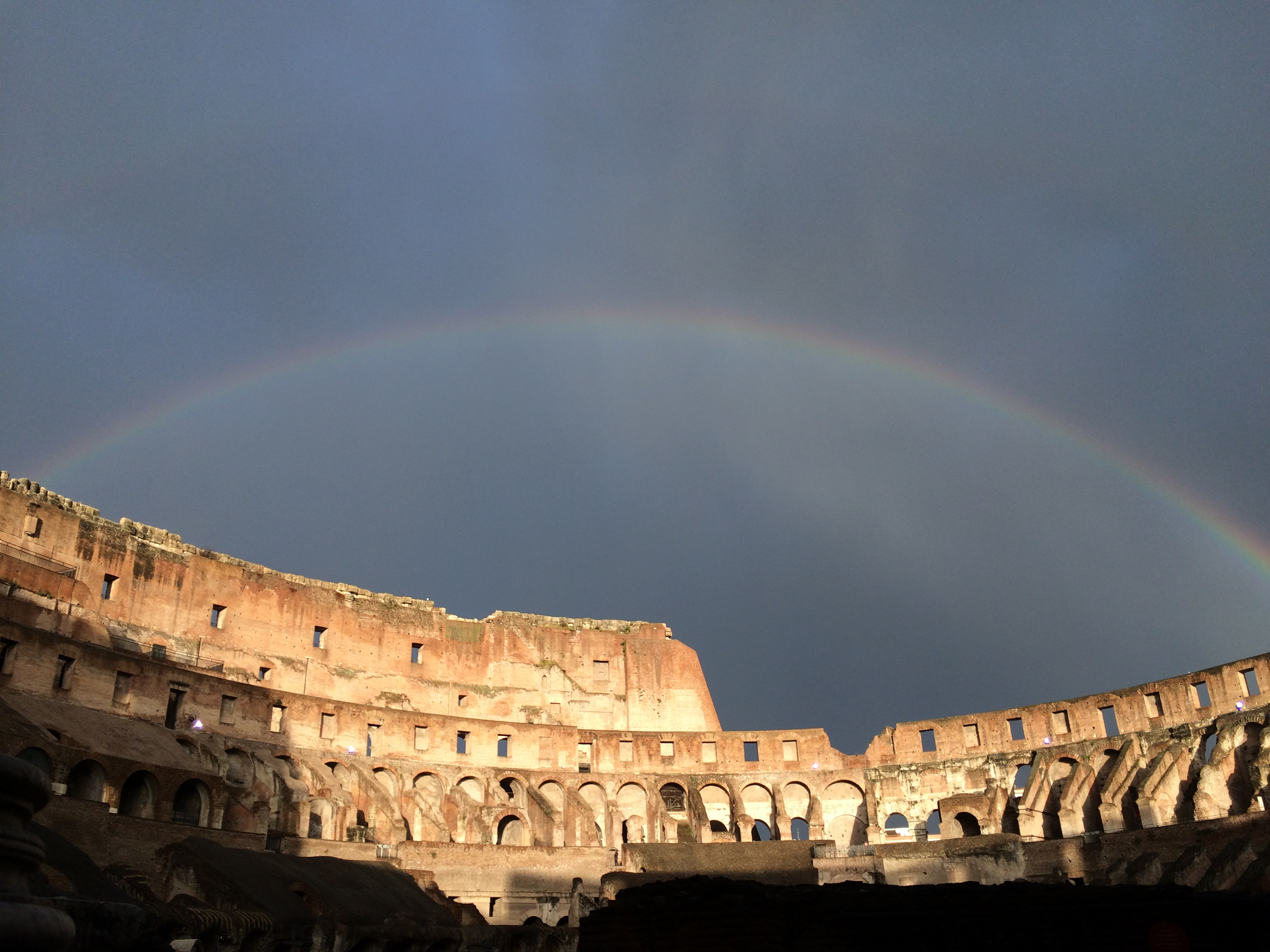 Rainbow above the Colosseum in Rome.  Sunshine and shadow in the foreground.  Cloud vapour streaking the sky.