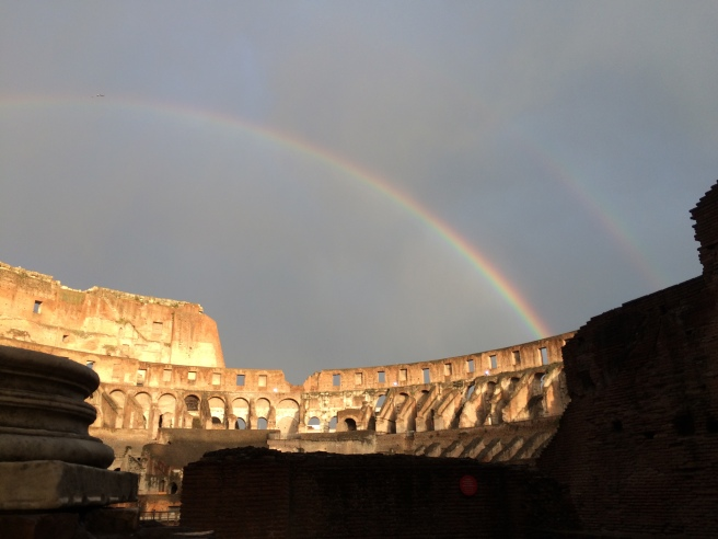Double Rainbow above the Colosseum in Rome.  Sunshine and shadow in the foreground.  Cloud vapour streaking the sky.